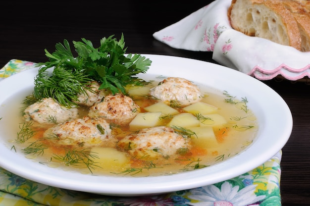Chicken broth of potatoes, carrots and meatballs sprinkled with dill