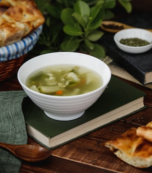 Chicken broth soup with vegetables inside a white bowl served with bread