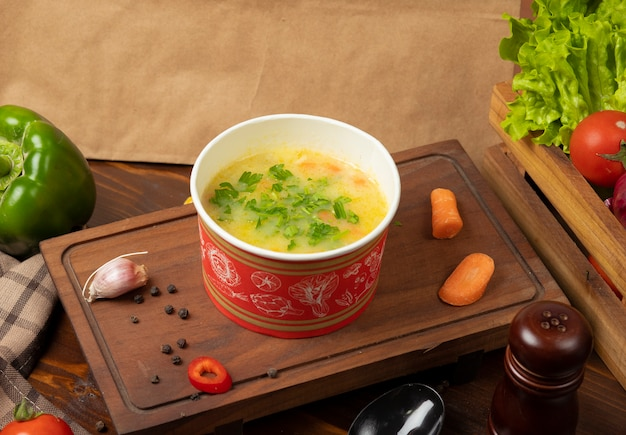 Chicken broth vegetable soup in disposable cup bowl served with green vegetables.