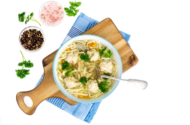 Chicken broth with egg noodles and meatballs.