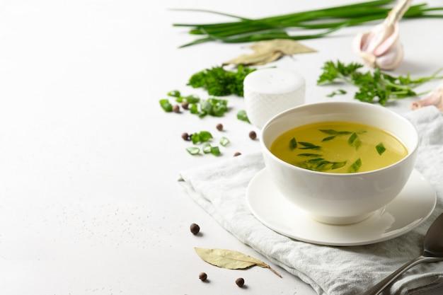 Куриный бульон с зеленым луком в белый шар на белом столе. копировать пространство