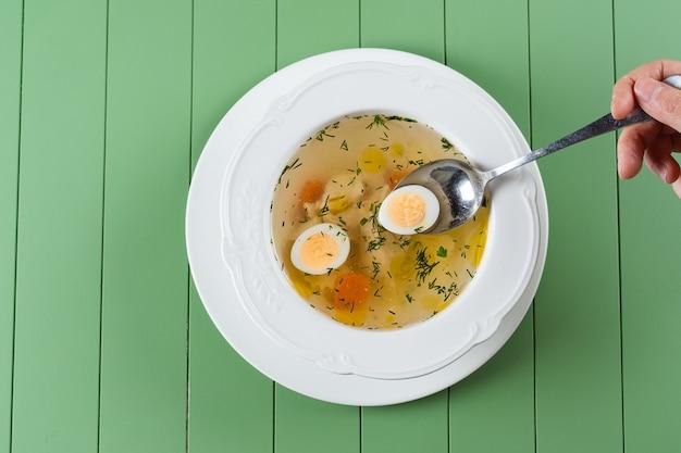 Куриный бульон с мясом, морковью, зеленью и перепелиным яйцом в белой тарелке на зеленом столе