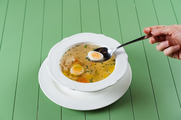 Chicken broth with meat, carrots, herbs and quail egg in a white plate on a green table
