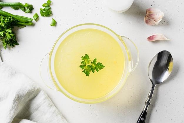 Куриный бульон с луком, зеленью в стеклянной посуде с ингредиентами.