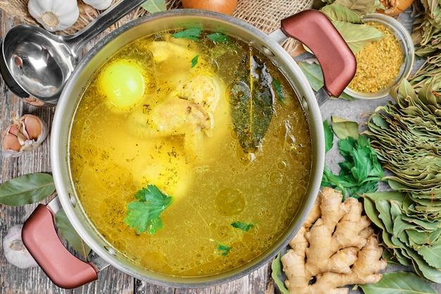 Куриный бульон с овощами и специями в кастрюле, ингредиенты для супа на деревянном столе