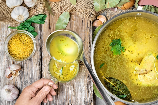 Chicken broth with vegetables and spices in a saucepan, ingredients for soup on a wooden table