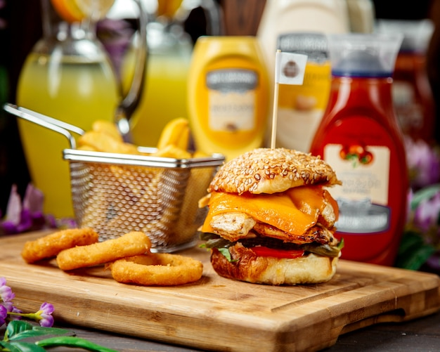 Chicken burger with cheddar served with french fries and sauce