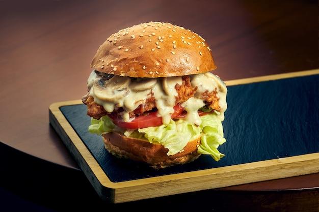 Куриный бургер с сыром, помидорами, луком и грибами на черной доске. быстрое питание