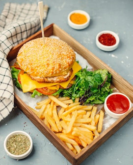 Chicken burger with french fries on wooden board