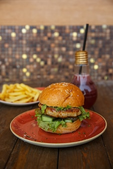 Chicken burger with fresh and pickled cucumber, lettuce and ketchup