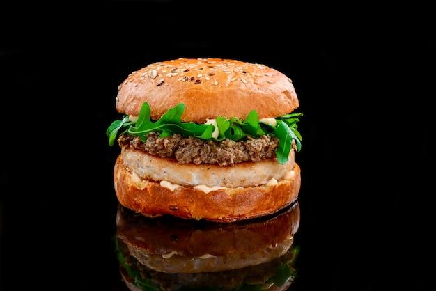 Куриный бургер с соусом и копченой телятиной на черной поверхности