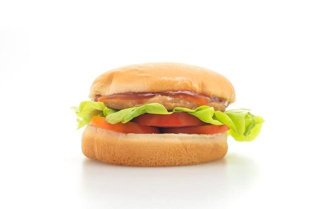 白い表面に分離されたソースとチキンバーガー