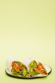 Chicken burrito wrap on plate against mint green background