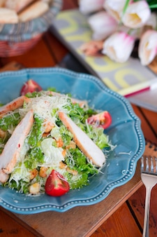 Chicken caesar salad with chopped parmesan cheese fresh lettuce and tomatoes
