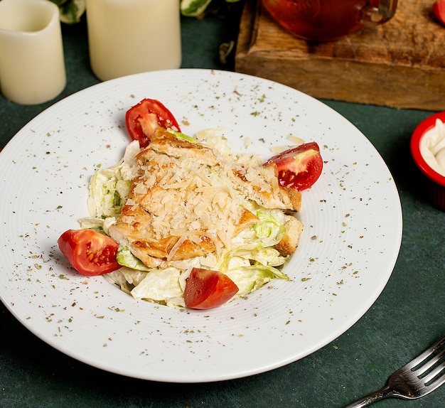 Chicken caesar salad with chopped parmesan, lettuce and tomatoes