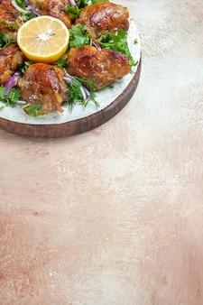 Chicken chicken herbs onion lemon on the wooden cutting board
