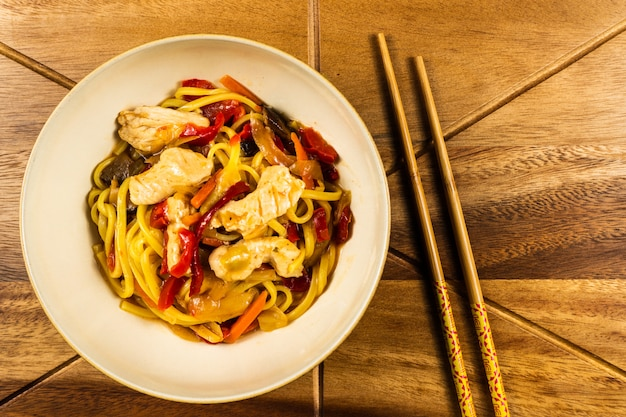 Chicken chow mein and chopsticks on wooden table