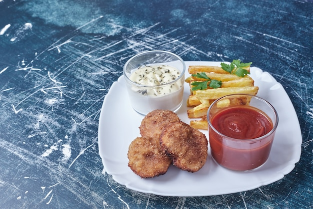 Chicken cotlets with french fries and ketchup.