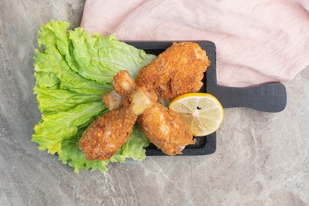 Хрустящие куриные ножки с листьями салата и лимоном на темной доске.
