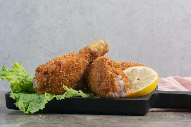 Cosce croccanti di pollo con lattuga e limone su tavola scura.