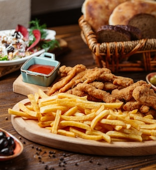 Chicken croquettes served with french fries on wooden platter and fresh salad