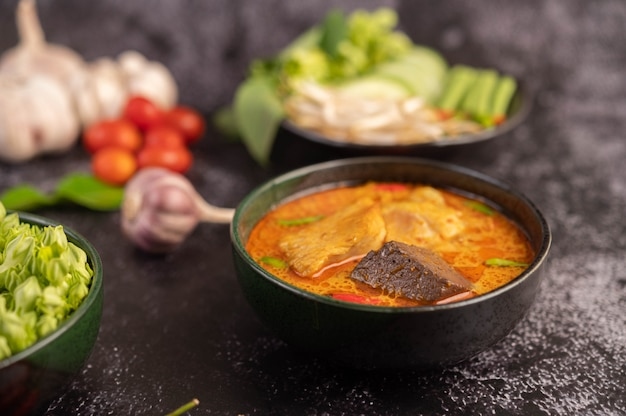 Chicken curry in a black cup with rice noodles.