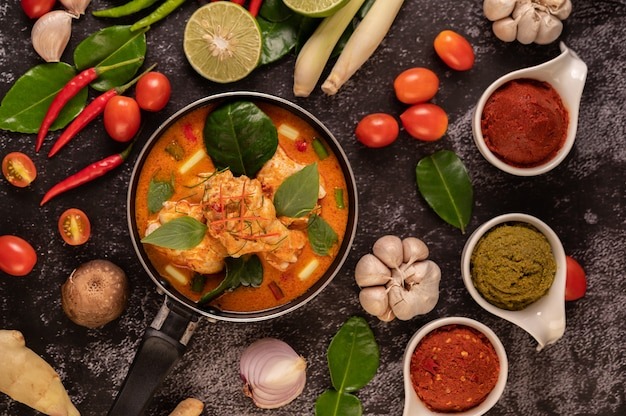 Chicken curry in a pan with lemongrass, kaffir lime leaves, tomatoes, lemon, and garlic