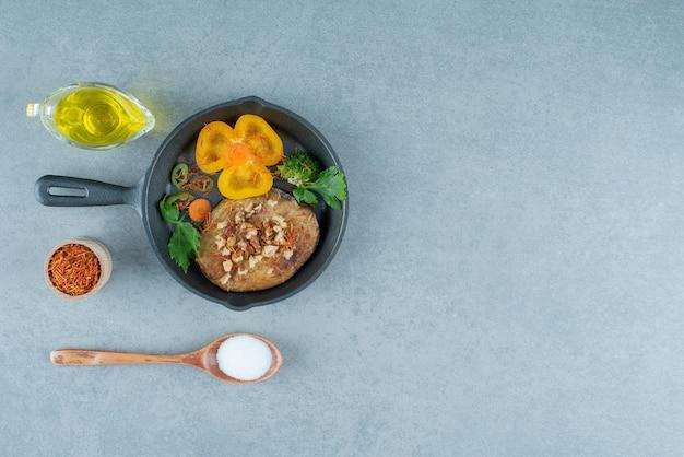 Куриная котлета на черной сковороде с маслом и солью.