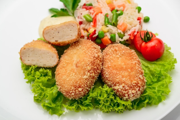 리조또와 야채를 곁들인 반죽에 치킨 커틀릿. 흰 바탕.