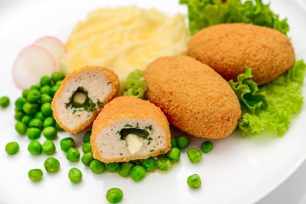 으깬 감자와 완두콩과 함께 제공되는 버터와 허브로 채워진 빵가루에 치킨 커틀릿