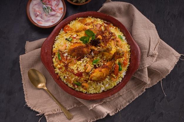 Курица дум бирияни с рисом джира и специями, выложенная в глиняной посуде