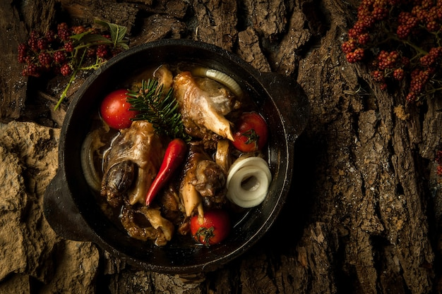 Chicken dish with vegetables in a frying pan on the background of tree bark