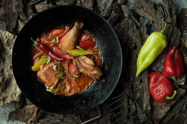 Куриное блюдо с овощами на сковороде на фоне коры дерева
