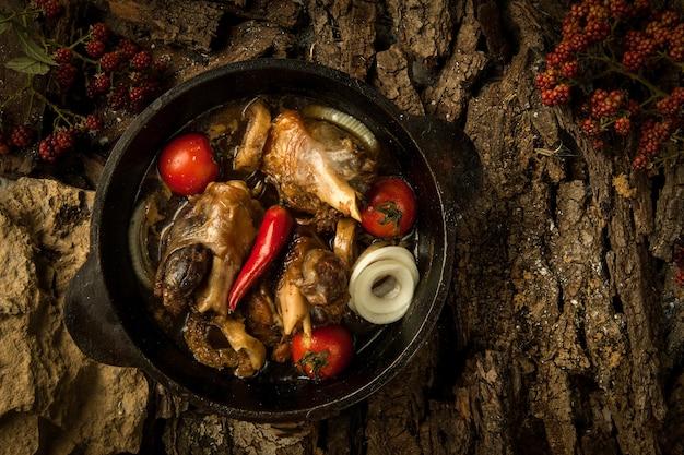 木の樹皮の背景にフライパンで野菜と鶏肉料理