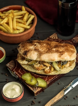 Chicken doner in bread stuffed with pickled cucumber served with fries