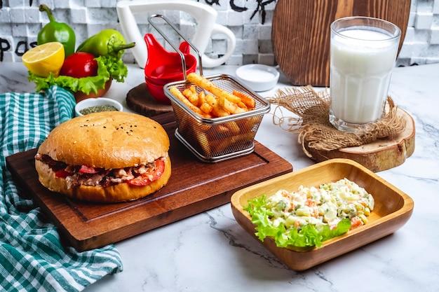 Куриный донер в хлебе с картофелем фри на доске столичный салат и стакан кефира