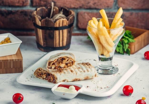 Куриный донер в лаваше с картофелем фри в тарелке