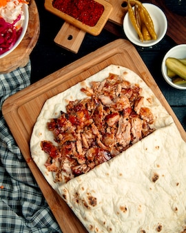 Chicken doner kebab in flatbread served with pickled cucumber and pepper