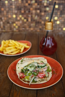 Chicken doner with lettuce, cucumber, tomato and herbs in pita bread