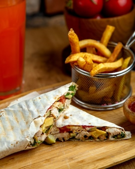 Chicken doner wrap in flatbread served with french fries