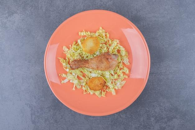 Куриная голень и жареный картофель на оранжевой тарелке.