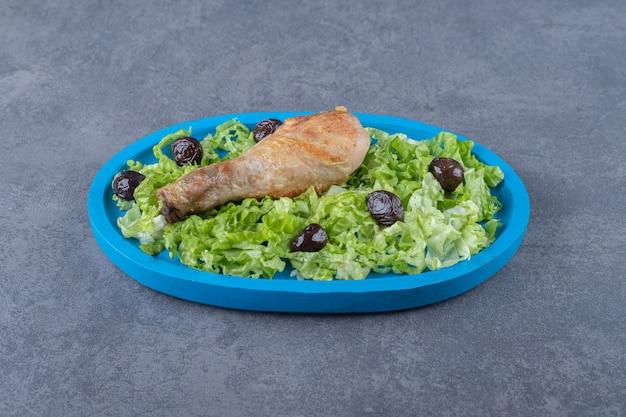 Coscia di pollo, olive e lattuga sul piatto blu.