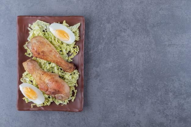 Куриные голени и вареные яйца на коричневой тарелке.