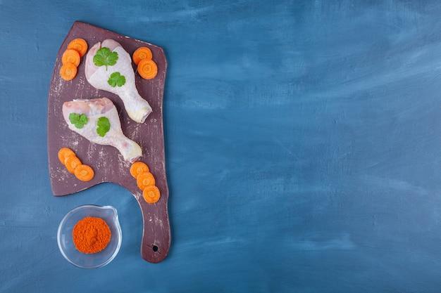 青いテーブルの上にまな板の上に鶏のドラムスティックとスライスしたニンジン。