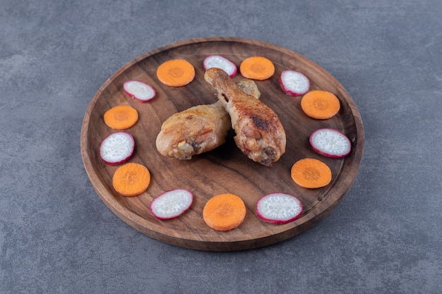 Куриные голени и нарезанные овощи на деревянной тарелке.