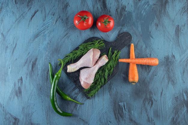 青い表面のまな板の上に鶏のモモ肉と野菜。