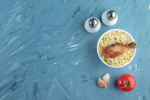 Cosce di pollo e noodle in una ciotola accanto a sale, pomodori e aglio, sullo sfondo di marmo.
