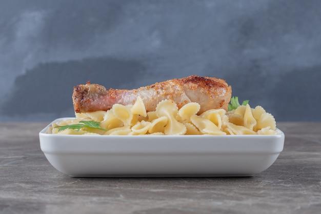 Cosce di pollo sulla pasta nella ciotola, sulla superficie di marmo.