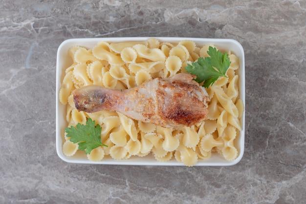 Cosce di pollo sulla pasta nella ciotola, sul marmo.