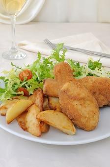 감자와 샐러드를 곁들인 빵가루를 곁들인 치킨 나지만